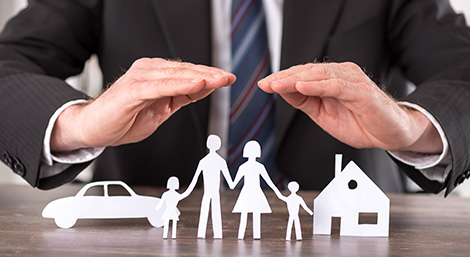 Insurance Agent Holding Hands over Family Cutouts